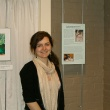 Ceilidh posing with exhibit photos and information panel
