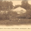 black and white postcard of large greenhouse with gardens in front