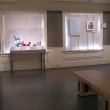 Gallery view of display case with Homework House student artwork.