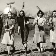 five students carrying rakes